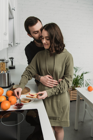 beautiful young couple preparing toasts during breakfast in kitchen