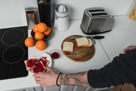 cropped view of man preparing toasts with jam during breakfast in kitchen