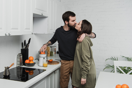 beautiful young couple making orange juice, hugging and kissing during breakfast in kitchen