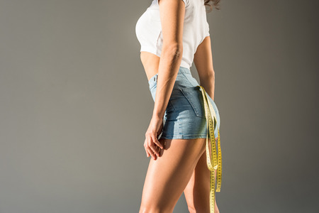 cropped view of woman standing in blue tight denim shorts with measuring tape in pocket isolated on grey Stock Photo
