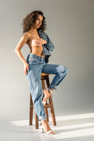 sexy naked woman covering breast with hand while sitting on chair on grey background Stock Photo - 117387257
