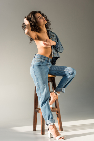 sexy naked woman with curly hair covering breast with hand while sitting on chair on grey background 写真素材