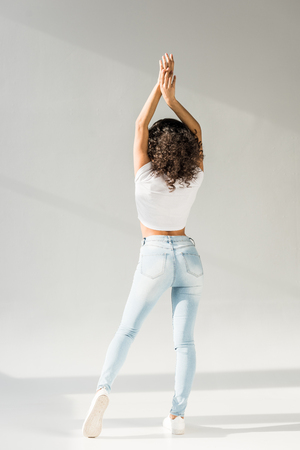 back view of woman posing with hands above head in tight blue jeans on grey background