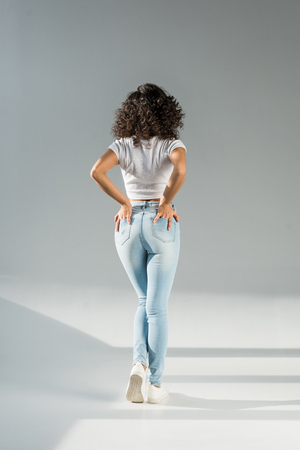 back view of woman standing with hands in pockets in tight blue jeans on grey background Imagens