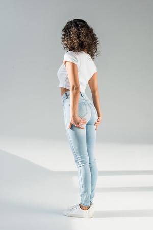 Rückansicht einer Frau, die in engen Jeans auf grauem Hintergrund steht standing