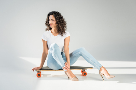 attractive woman with curly hair sitting on skateboard in high heels on grey background Imagens