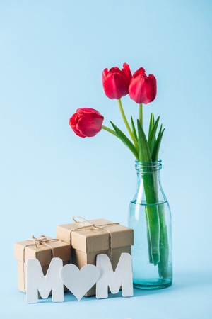 gift boxes, bouquet of red tulips and paper word mom with heart shaped litter