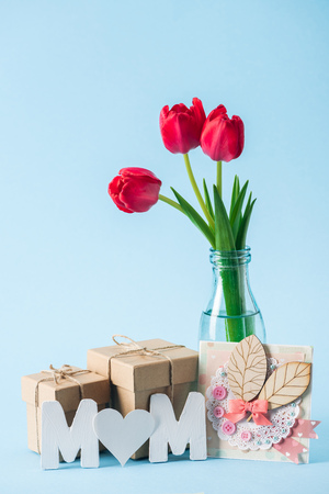 mothers day greeting card, gift boxes, bouquet of red tulips and paper word mom with heart shaped litter