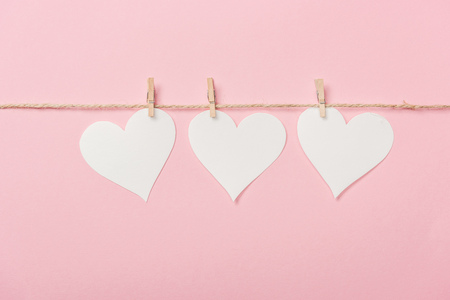 white paper hearts with coarse thread on pink background Reklamní fotografie