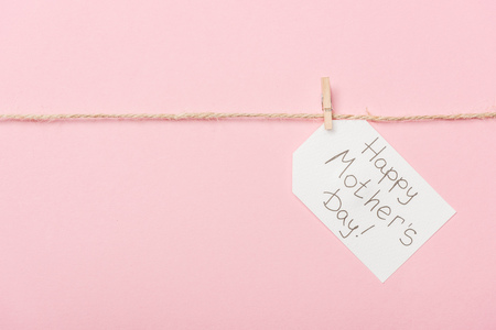 white paper label with happy mothers day greeting with coarse thread on pink background