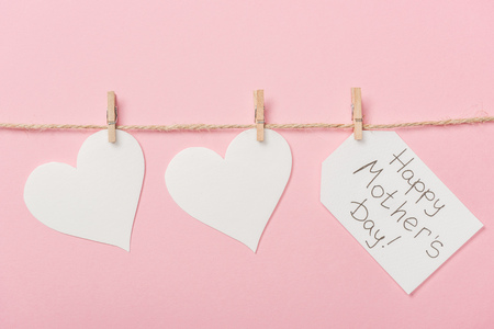 white paper hearts and label with happy mothers day greeting with coarse thread on pink background