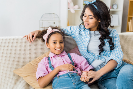smiling african american woman sitting on sofa with adorable daughter Stock Photo