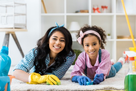 smiling african american woman and daughter in bright rubber gloves lying on carpet