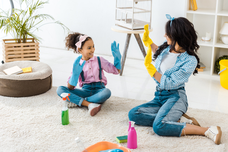 african american mom and cute daughter in bright rubber gloves having fun while sitting on carpet Stock Photo