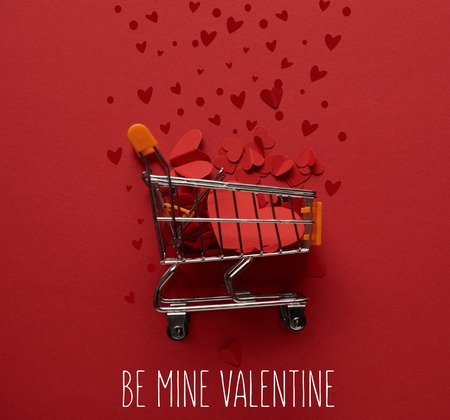 top view of toy shopping cart with decorative paper cut hearts on red background with be mine valentine lettering 版權商用圖片
