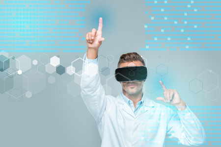 scientist in virtual reality headset touching medical interface isolated on grey, artificial intelligence concept Фото со стока