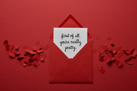 top view of envelope with first of all, you are really pretty lettering, with paper cut hearts on red background