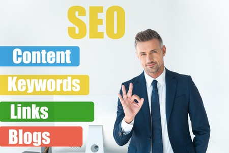 handsome businessman showing okay gesture and looking at camera isolated on white with seo symbols