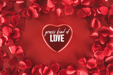 top view of beautiful heart with groovy kind of love lettering and decorative petals on red background, valentines day concept Фото со стока