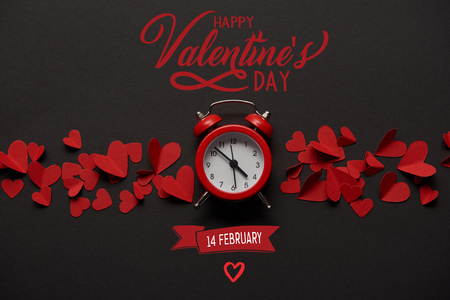 top view of clock and red paper cut decorative hearts on black background with Happy valentines day, 14 february lettering