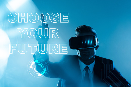 businessman in virtual reality headset pointing on choose your future lettering isolated on blue, artificial intelligence concept