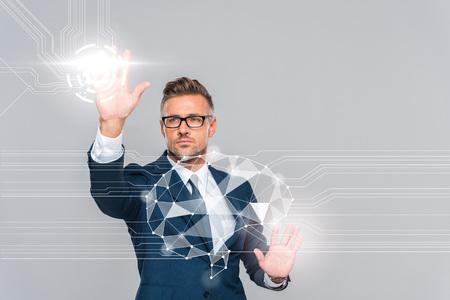 Gut aussehender Geschäftsmann in blauem Anzug und Brille, der das Gehirn berührt, isoliert auf grauem, künstlichem Intelligenzkonzept