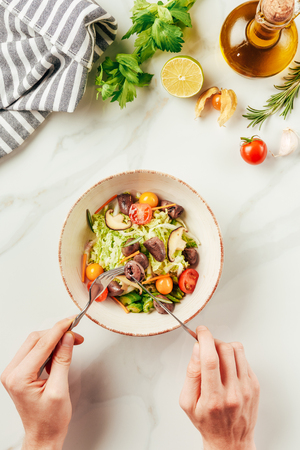 cropped  view of woman eating salad with fork and knife Stock Photo