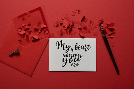 top view of envelope with my heart is wherever you are lettering , paper cut hearts and pen on red background