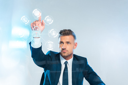 handsome businessman pointing on icons isolated on white, artificial intelligence concept