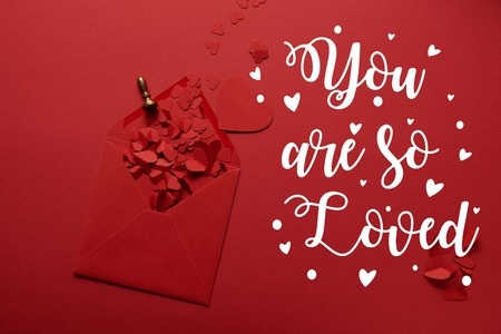 top view of paper cut hearts and opened envelope on red background with you are so loved lettering