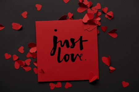 top view of red greeting card with just love lettering and paper cut hearts on black background