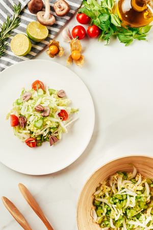 salad, cabbage and celery in plate with bottle of oil, cherry tomatoes, lime and mushrooms