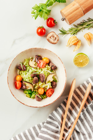 salad on white bowl with bottle of oil, cherry tomatoes, lime and rosemary on table