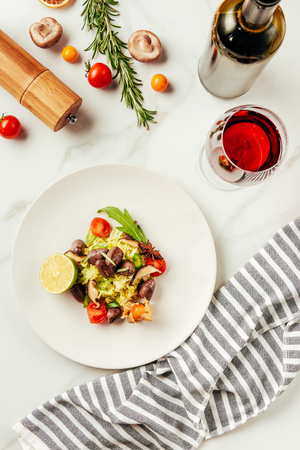 top view of salad on white plate with glass and bottle of wine and cloth