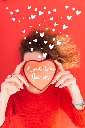 top view of girl holding heart symbol with love is in the air lettering in front of face isolated on red, st valentines day concept