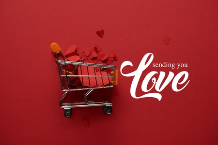 top view of toy shopping cart with decorative paper cut hearts on red background with sending you love lettering