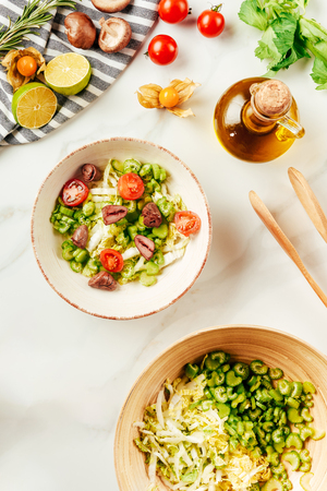 top view of salad, cabbage and celery in bowls with bottle of oil, cherry tomatoes, limes and mushrooms Stock Photo