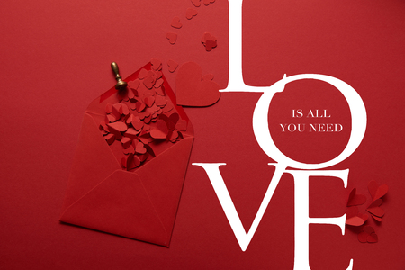 top view of paper cut hearts and opened envelope on red background with Love is all you need lettering