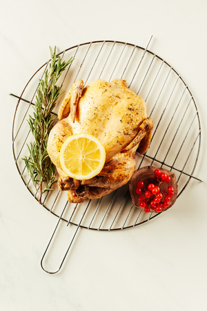 top view of fried chicken, rosemary and berries on metal grille with lemon on white table
