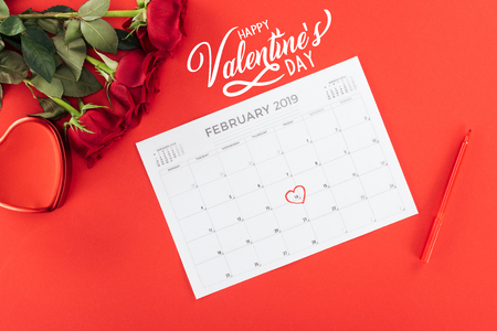 top view of roses and calendar with 14th february date marked with heart isolated on red with Happy valentines day lettering