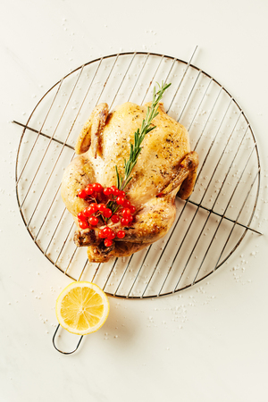 top view of fried chicken, rosemary and berries on metal grille with lemon Zdjęcie Seryjne