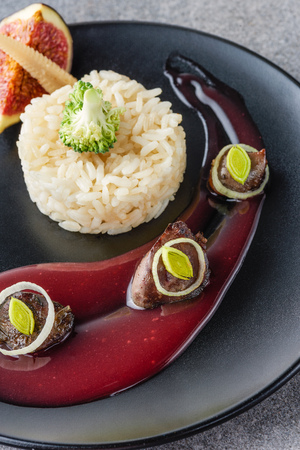 close up of rice, broccoli, fig and fried meat with sauce on black plate Stock Photo