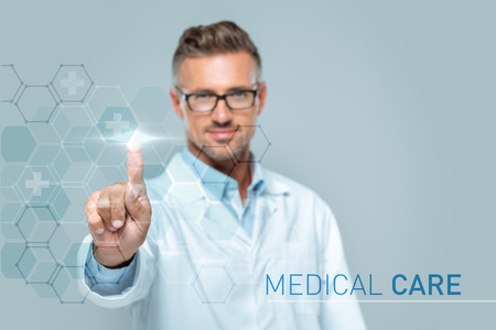 selective focus of handsome scientist touching medical care interface in air isolated on white, artificial intelligence concept Stock fotó