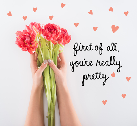 "cropped view of woman holding tulips in hands isolated on white with ""first of all, you are really pretty"" lettering"