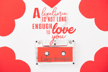 top view of audio cassette with love songs lettering and heart shaped cards isolated on white, st valentines day concept with a lifetime is not long enough to love you lettering