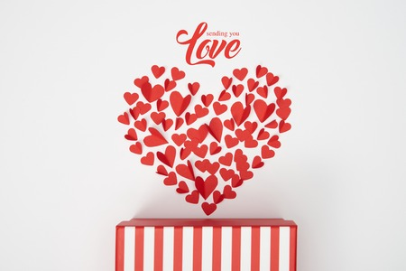top view of heart shaped arrangement of small red paper cut hearts and striped gift box on white background with sending you love lettering