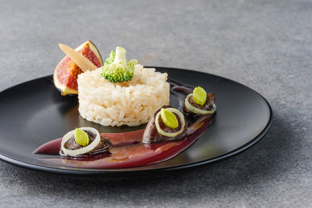 rice, broccoli, fig and fried meat with sauce on black plate and stone surface