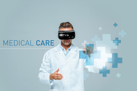 scientist in virtual reality headset touching medical care interface isolated on grey, artificial intelligence concept Stock fotó