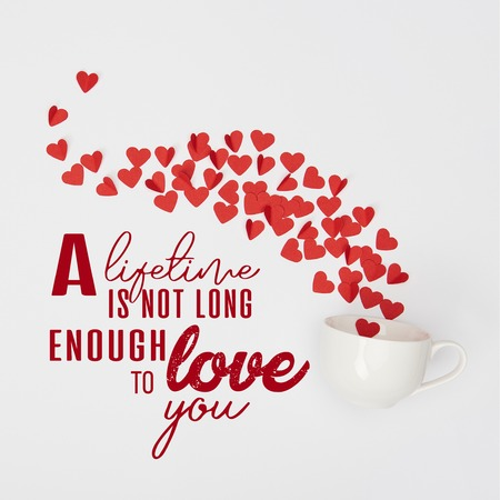 top view of cup and heap of red paper cut hearts on white background with a lifetime is not long enough to love you lettering Stock Photo