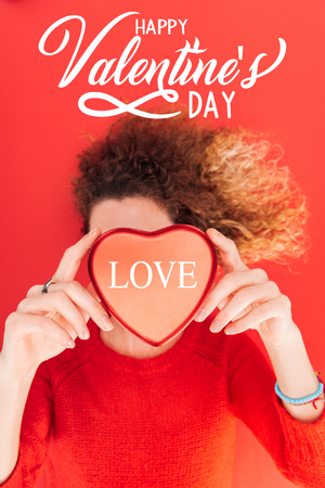 top view of girl holding heart symbol with love lettering in front of face isolated on red, happy valentines day concept